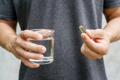 man holding glass of water and medicine